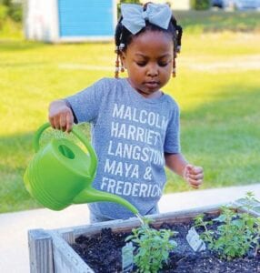 Grace waters the new herb garden provided by Keller Williams Palmetto.
